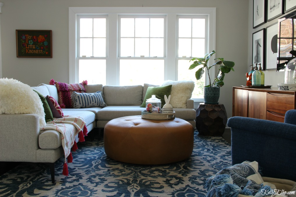 Beautiful and cozy family room with sectional sofa, leather ottoman, blue tassel rug and an eclectic mix of pillows and throws kellyelko.com #familyroom #homedecor #decorate #ottoman #sectional #bohodecor