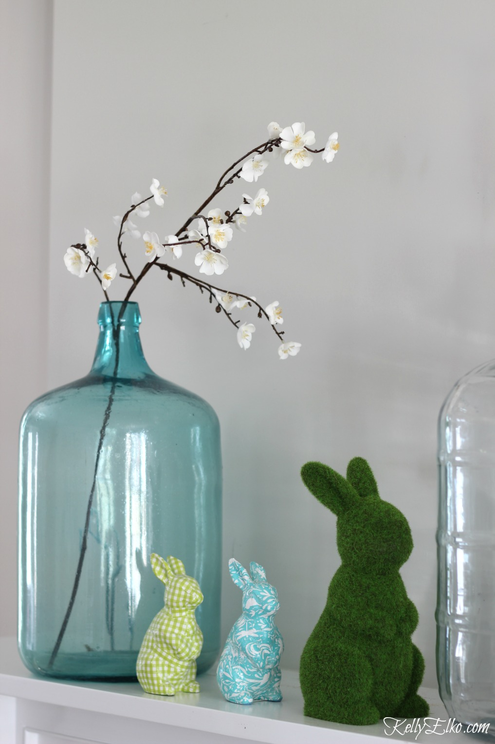 25 Spring Decorating Ideas - love this mantel with vintage glass demijohns and colorful bunnies kellyelko.com #spring #springdecor #homedecor #mantel #springmantel #vintagedecor #easterbunny
