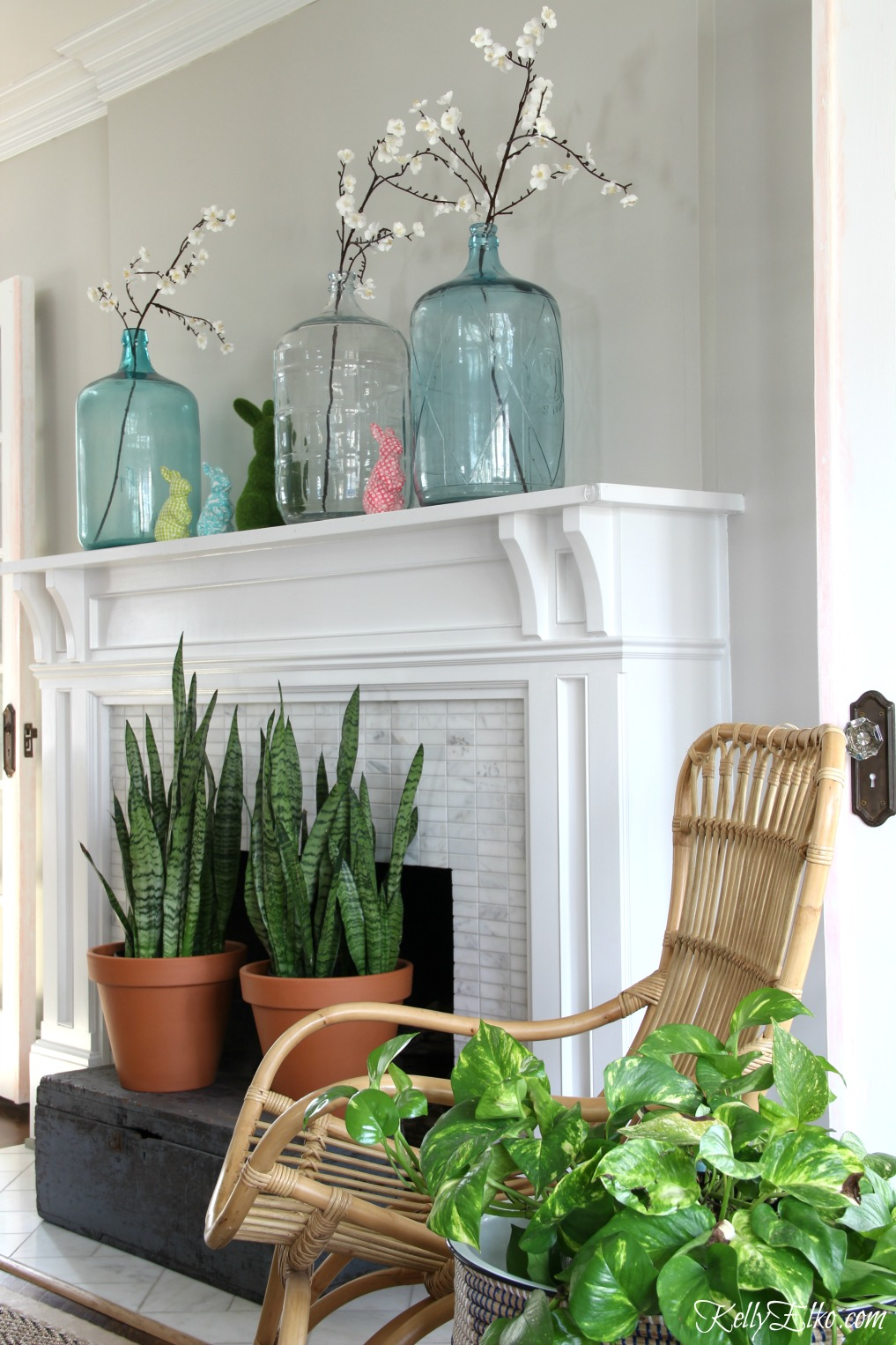 Spring Decorating Ideas - love this spring mantel with vintage demijohn jugs and colorful bunnies kellyelko.com #spring #springdecor #springmantel #vintagedecor #homedecor