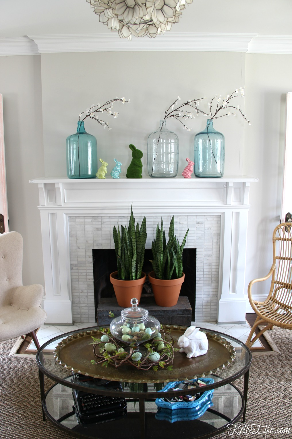 25 Spring Decorating Ideas - love this mantel with vintage glass demijohns, colorful bunnies and snake plants kellyelko.com #spring #springdecor #homedecor #mantel #springmantel #vintagedecor