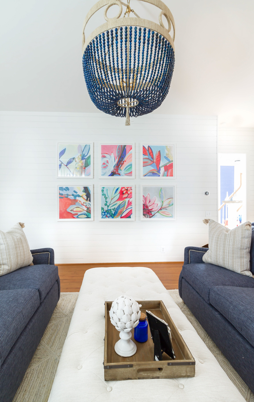 Eclectic Home Tour - love the white shiplap walls as a backdrop for a colorful gallery wall and statement chandelier #art #chandelier #lighting #livingroom