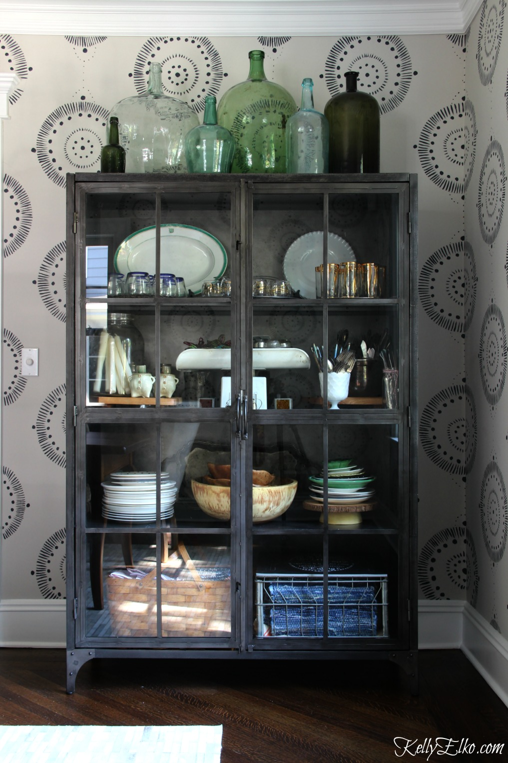 Forget wallpaper! This hand painted mural is like faux wallpaper minus the expense and I love the industrial metal cabinet and demijohn collection kellyelko.com #wallpaper #mural #diningroom #wallart #handpainted #collections #vintage