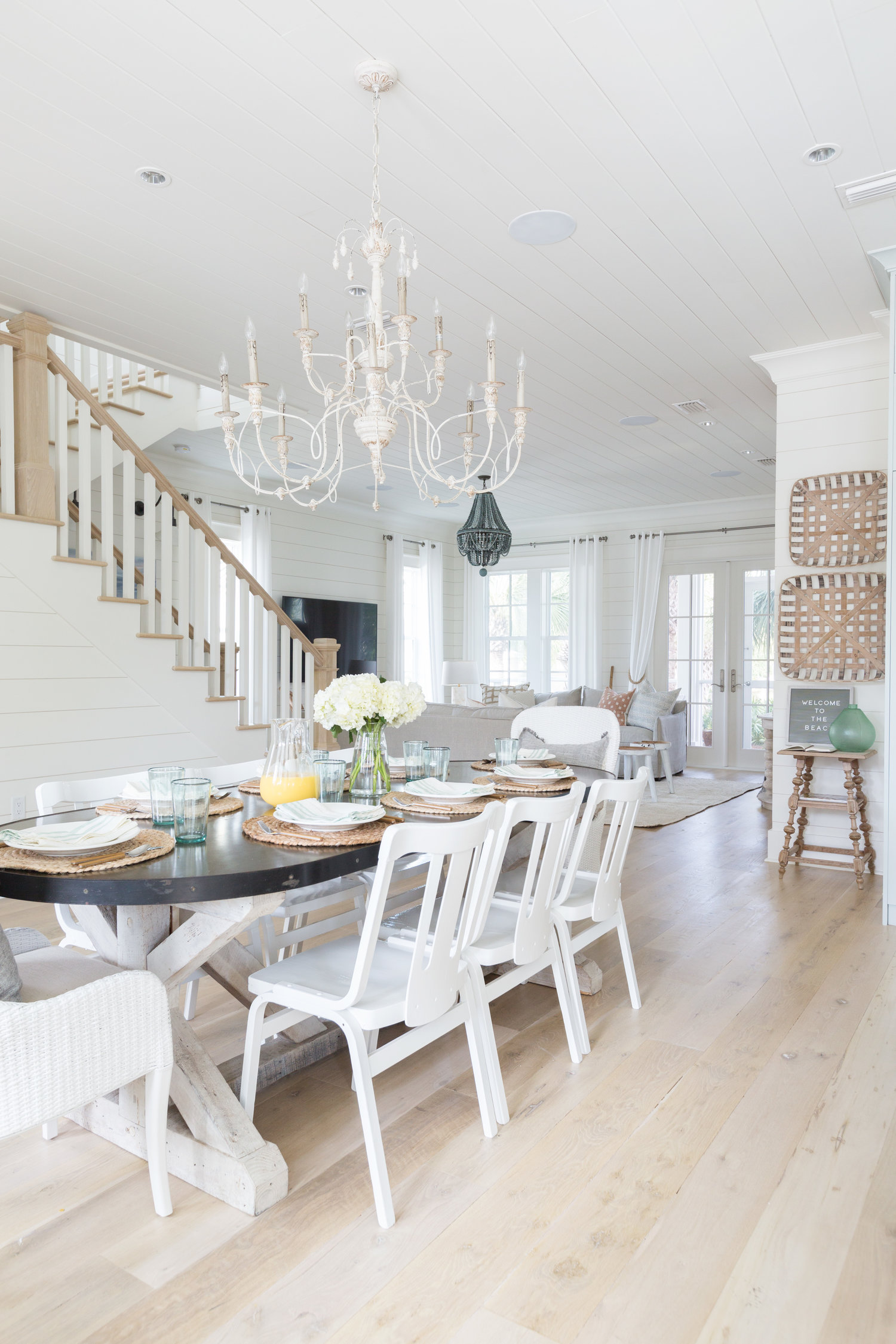 This beautiful home mixes ornate chandeliers with industrial table and farmhouse accessories kellyelko.com #farmhousestyle #interiors #chandelier #diningroom #kitchen #shiplap