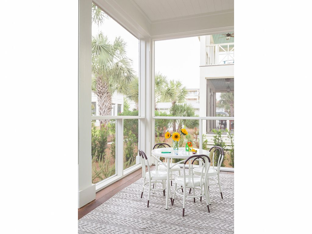 Beautiful screened in porch with bentwood chairs and a cozy rug kellyelko.com #porch #patio #interiors #decorate
