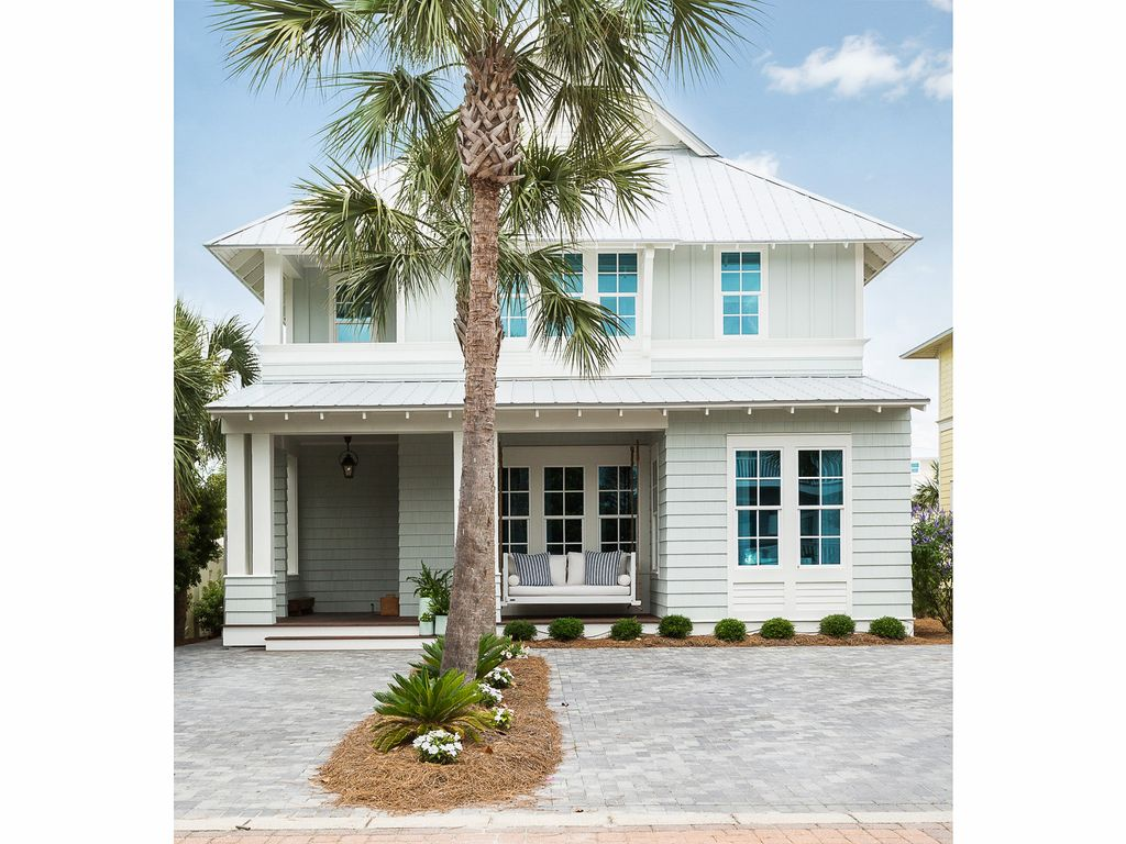 Eclectic Home Tour of the Sugar Palm House. Great curb appeal and love the hanging porch swing. kellyelko.com #hometour #decorate #coastalhome #florida