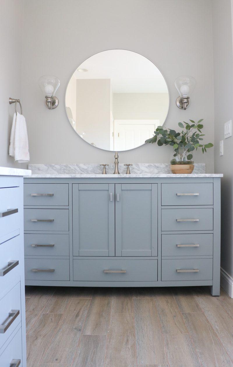 Beautiful blue bathroom vanity with large round mirror kellyelko.com #bathrooms #bathroomvanity #bathroomdecor