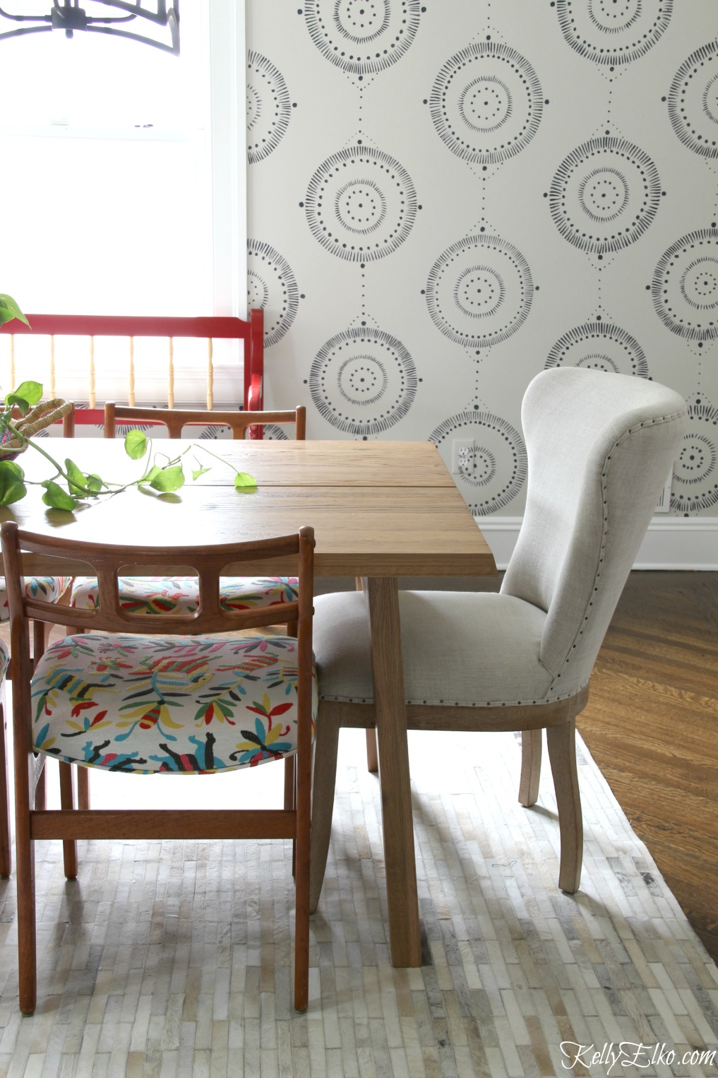 This eclectic dining room mixes Danish modern chairs with colorful otomi fabric and an Article dining table in solid oak kellyelko.com #diningroom #diningroomdecor #diningroomfurniture #midcenturymodern #midcentury #bohostyle #otomi #vintagestyle #interiordecor
