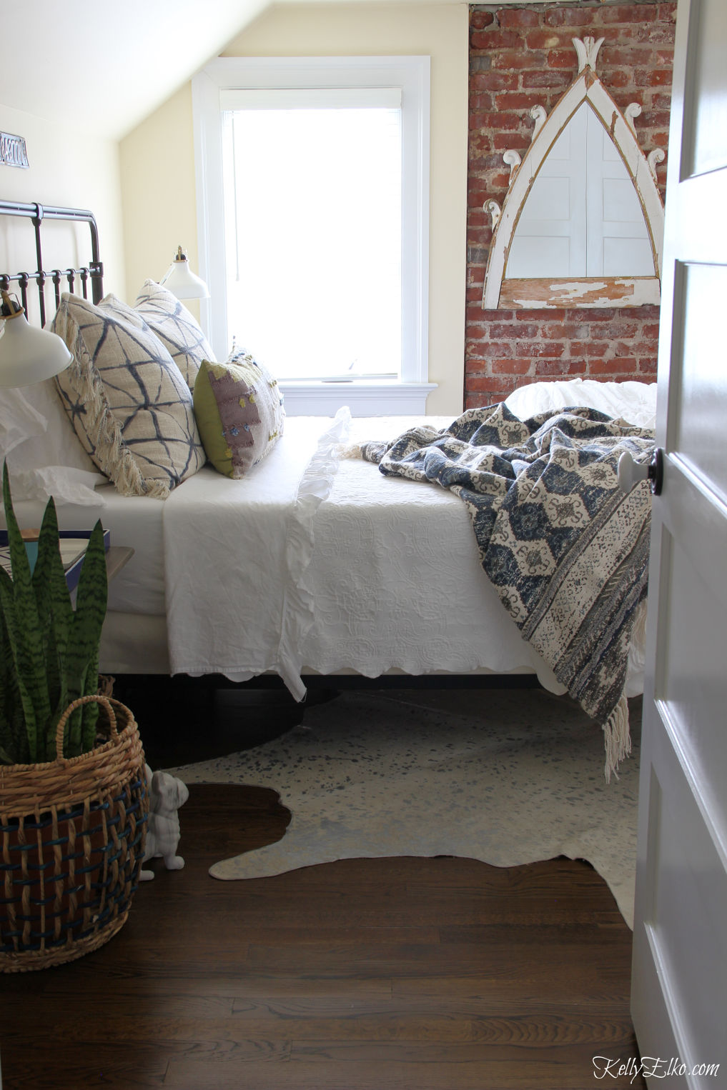 Guest bedroom decor - love the exposed brick wall and vintage style metal bed kellyelko.com #bedroom #bedrooms #bedroomdecor #interiordesign #vintagedecor #bohodecor