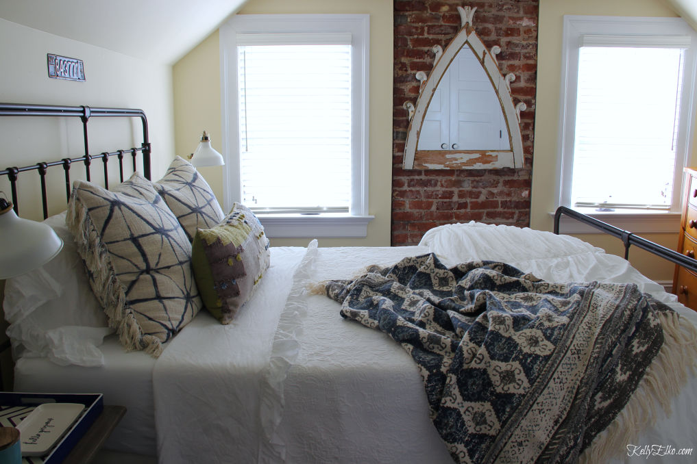 Guest Bedroom Decor - love the exposed brick wall and black iron bed and white bedding with lots of fun pillows kellyelko.com #bedroom #bedroomdecor #bedroomfurniture #bedroomdecorating #guestbedroom