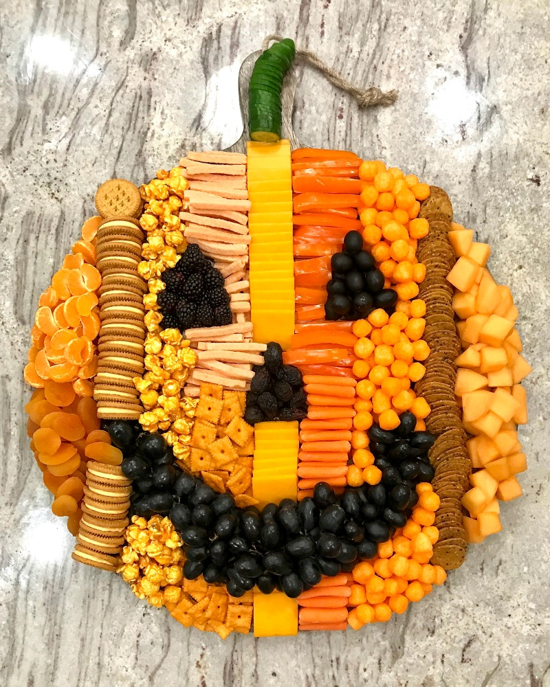 How fun is this pumpkin snack board! kellyelko.com #pumpkin #fallrecipes #fallfood #halloweenfood #halloweenparty #appetizers #fallsnacks