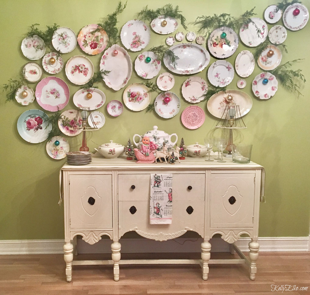 Shiny Brite Decorating Ideas - the most creative ideas for displaying Christmas ornaments like hanging from this plate wall kellyelko.com #vintagechristmas #christmasornaments #christmaswreath #christmasdecor #christmasdecorating #shinybrites #vintageornaments #ornaments #platewall #gallerywall #diningroom