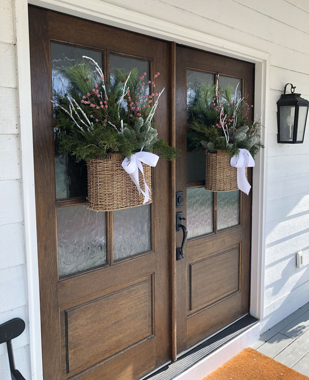 Beautiful baskets filled with greenery and berries replace traditional Christmas wreaths