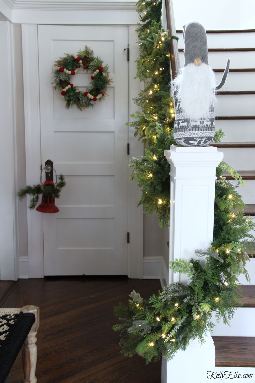 Love this succulent garland on the staircase kellyelko.com #christmas #christmasdecor #christmasfoyer #christmasbanister #christmasgarland #gnome #christmashometour