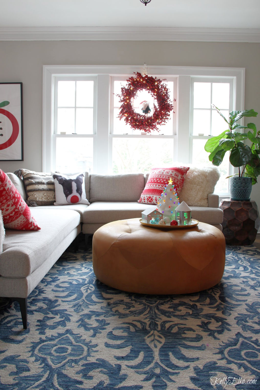 Love this cozy Christmas family room with Loloi rug and huge leather ottoman kellyelko.com #bohochristmas #christmaswreath #leatherottoman #christmasfamilyroom #redchristmas #christmasdecor #christmadecorations