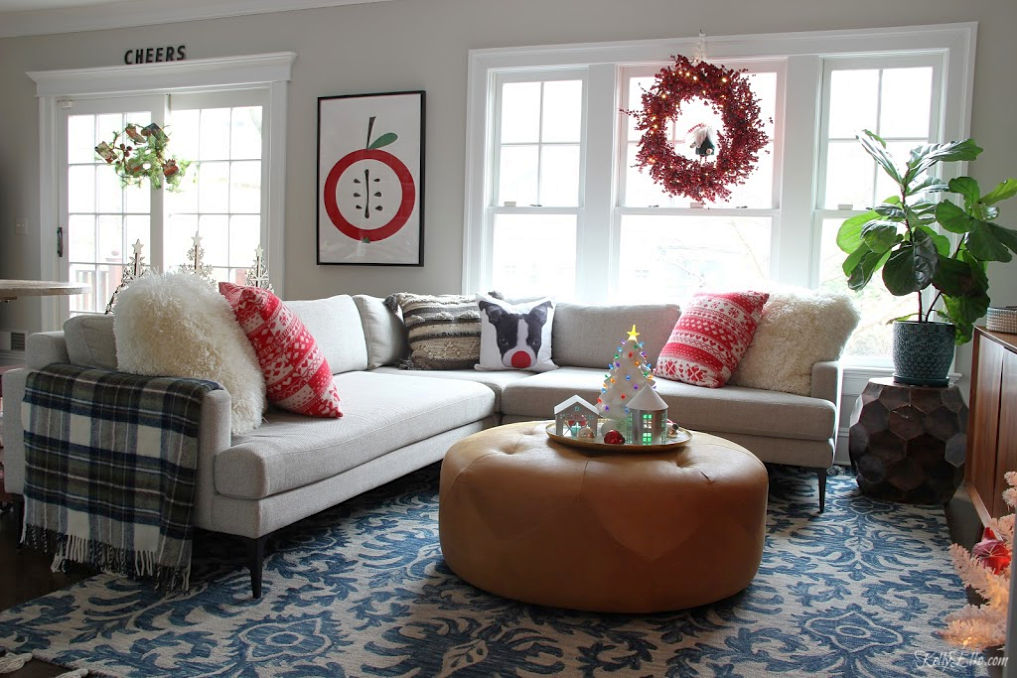 Cozy Christmas family room - love the Christmas dog pillow on the sectional sofa and huge berry wreath kellyelko.com #christmasdecor #christmaspillows #chritmaswreath #cozychristmas #leatherottoman #loloirug #modernart #fiddleleaffig
