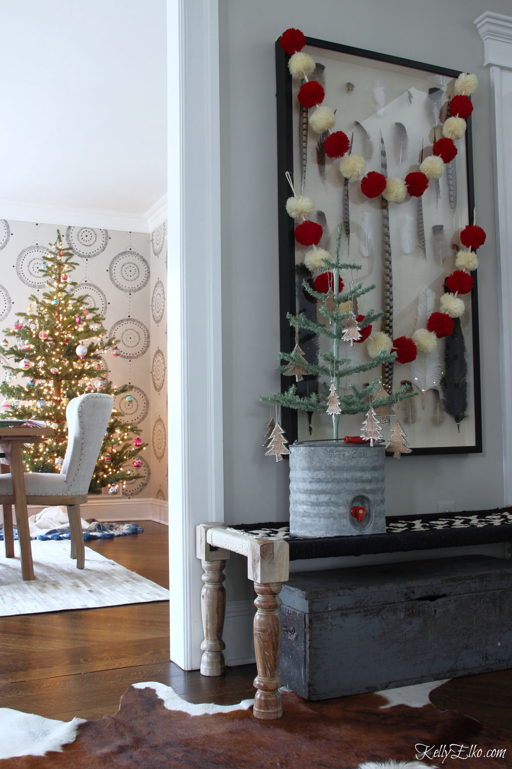 Beautiful Christmas home tour - love the pom pom garland hung over the art and the sparse Christmas tree kellyelko.com #christmas #christmasdecor #christmastree #christmasfoyer #christmasgarland #pompom #farmhousechristmas #vintagechristmas