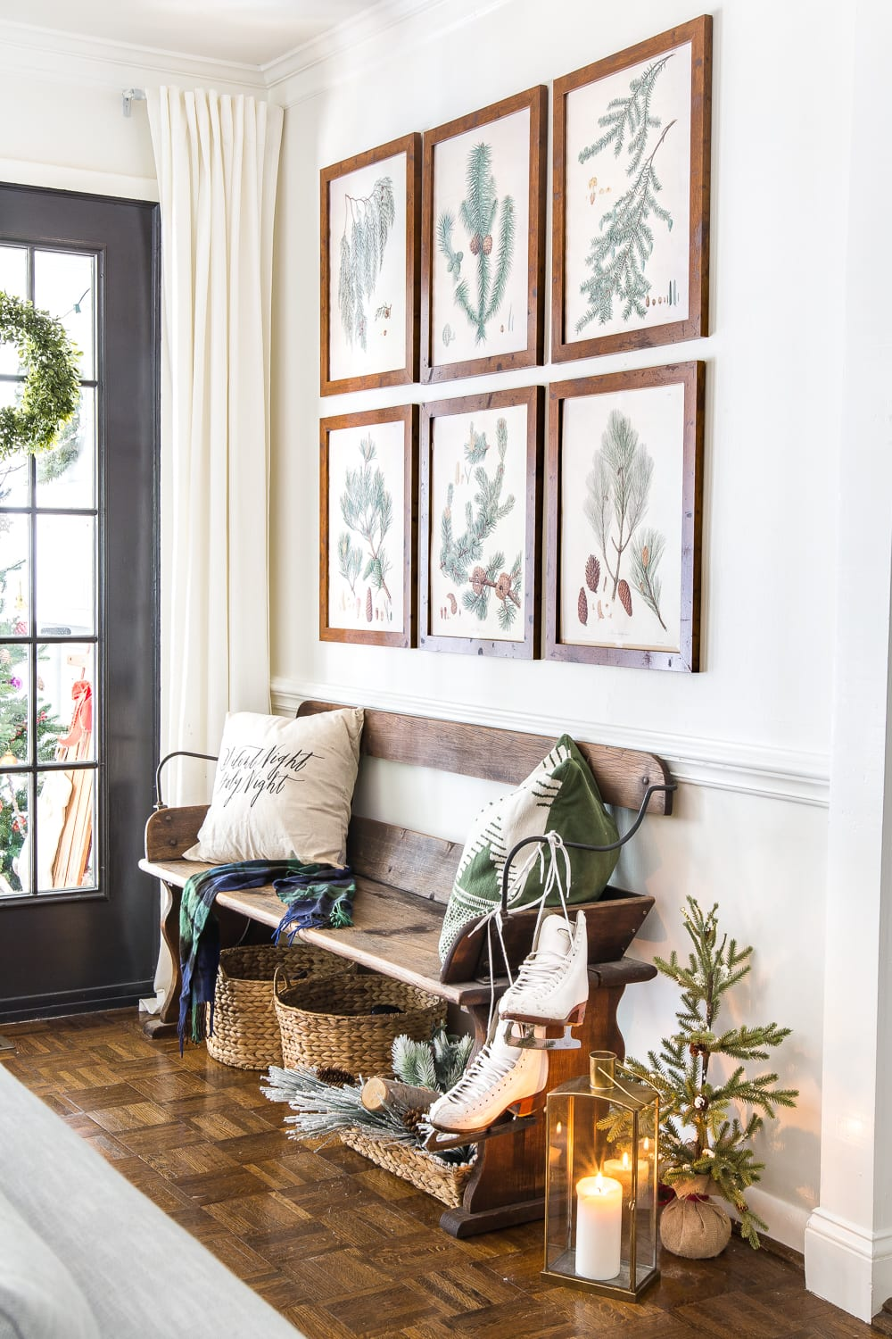 Beautiful Christmas entry with evergreen botanical gallery wall