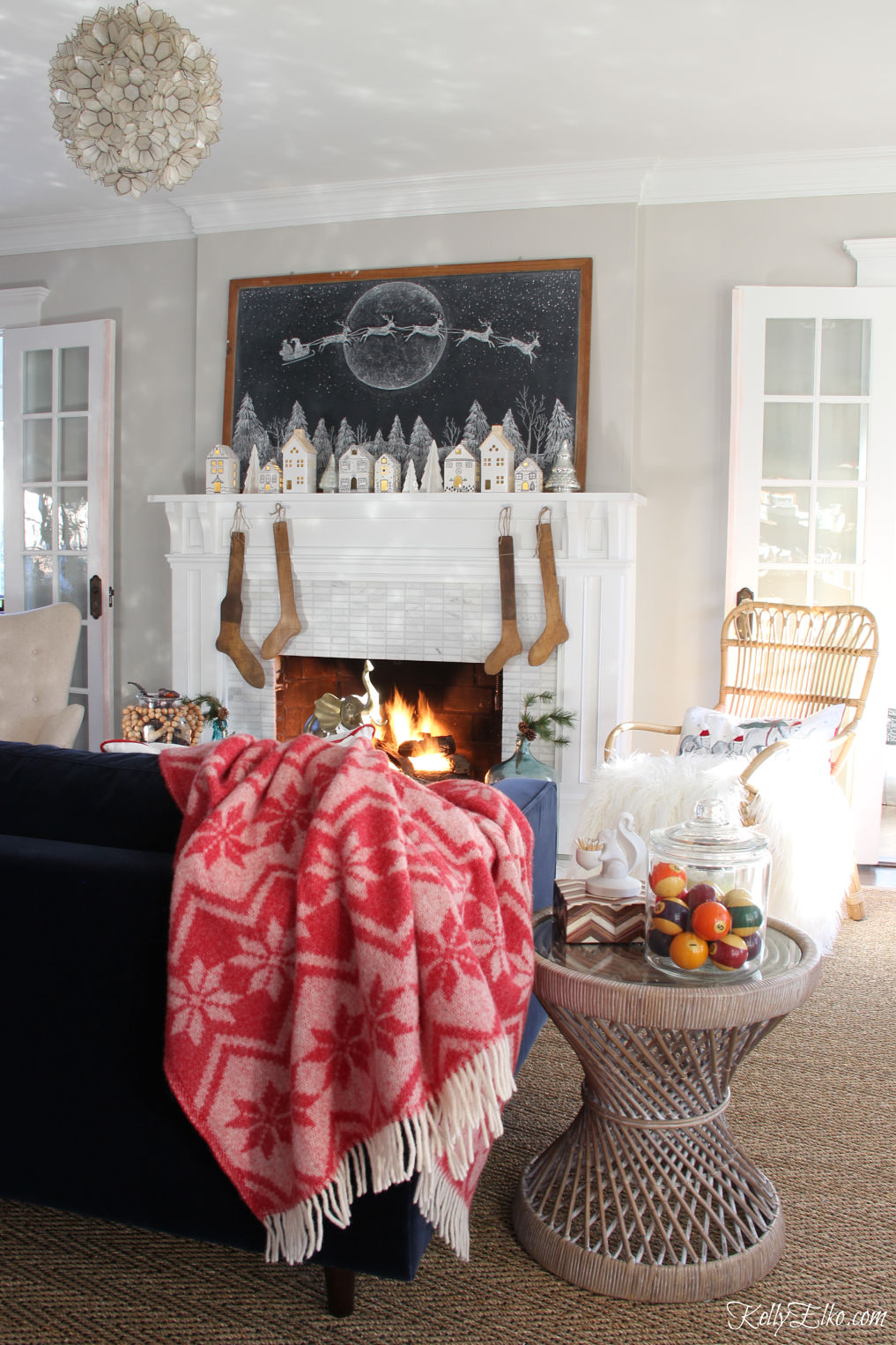 Beautiful Christmas home tour - love the giant Christmas chalkboard art and little houses on the mantel kellyelko.com #christmas #christmasdecor #christmasdecorating #christmasmantel #christmaslivingroom #farmhousechristmas #vintagechristmas #cozychristmas #livingroomdecor