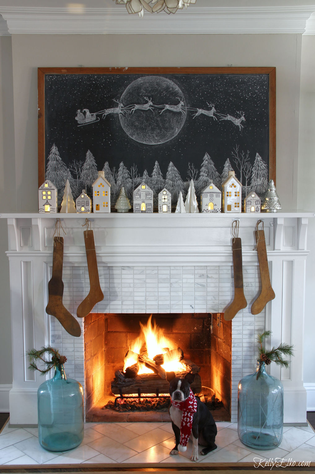 Love this chalkboard Christmas mantel with Santa in his sleigh, little white ceramic houses and antique stocking stretchers kellyelko.com #christmas #christmasmantel #farmhousechristmas #christmaschalkboard #chalkboardart #christmasdecorating #christmashometour #vintagechristmas