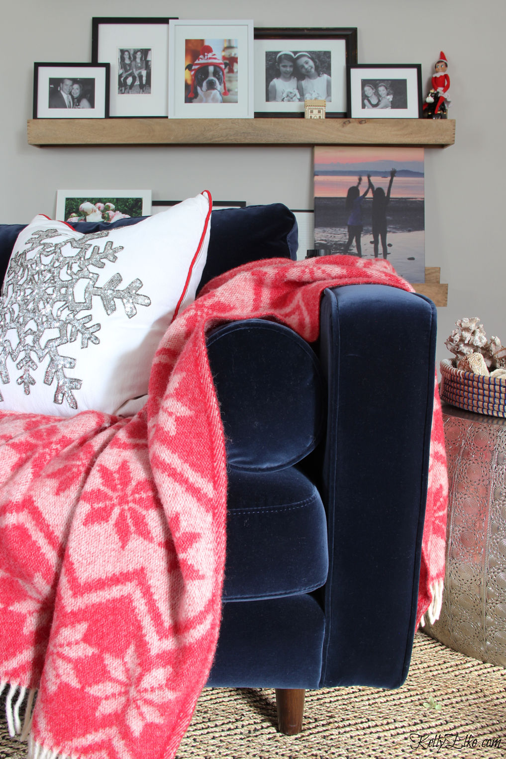 Love this cozy blue velvet sofa with red throw and the gallery wall of family photos kellyelko.com #christmas #christmasdecor #bohochristmas #christmaspillows #gallerywall