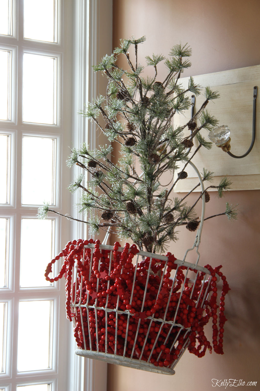 Love this Christmas tree in a wire basket filled with red garland kellyelko.com #christmastree #christmasdecor #christmasgarland #christmasdecorations #farmhousechristmas
