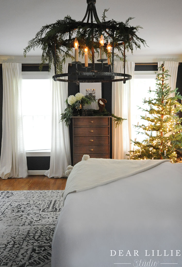Love this Christmas bedroom with garland on the chandelier