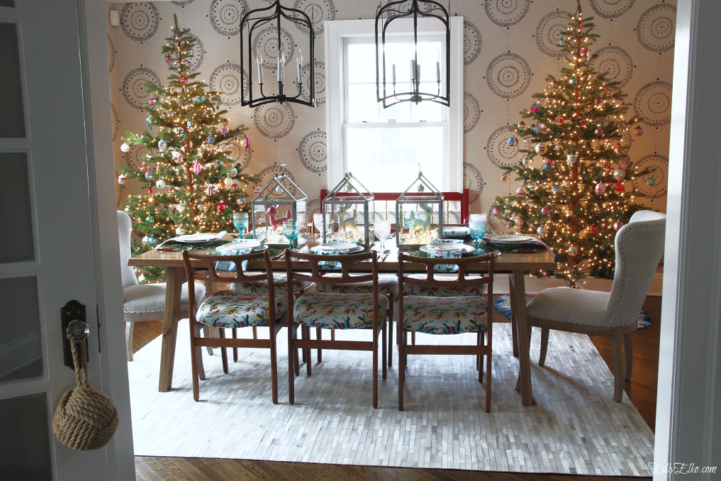 Love this Christmas dining room with a pair of sparse Christmas trees filled with vintage ornaments and the table setting is such a fun retro idea kellyelko.com #christmasdecor #christmasdecorations #christmastrees #christmaslights #christmasdiningroom #vintagechristmas #retrochristmas #colorfulchristmas #gofinding #ltkholiday