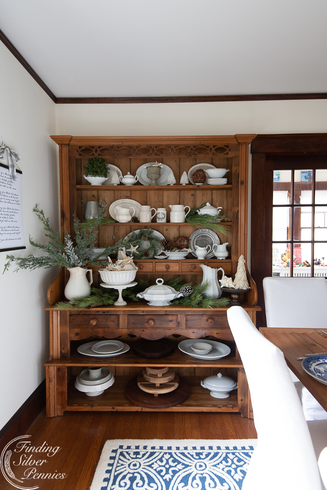 Love this beautiful pine hutch filled with white serving pieces and fresh greenery for Christmas