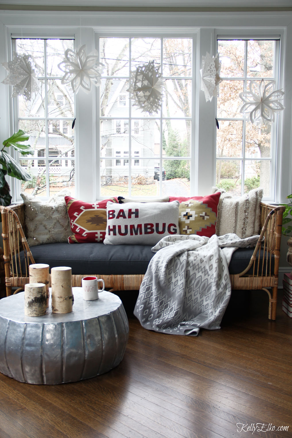 Love this Christmas sunroom with paper snowflakes hanging above a boho rattan daybed kellyelko.com #christmas #christmasdecor #christmasdecorating #christmaspillows #boho #bohodecor #eclecticdecor #interiordecor #interiordecorate #sunroom