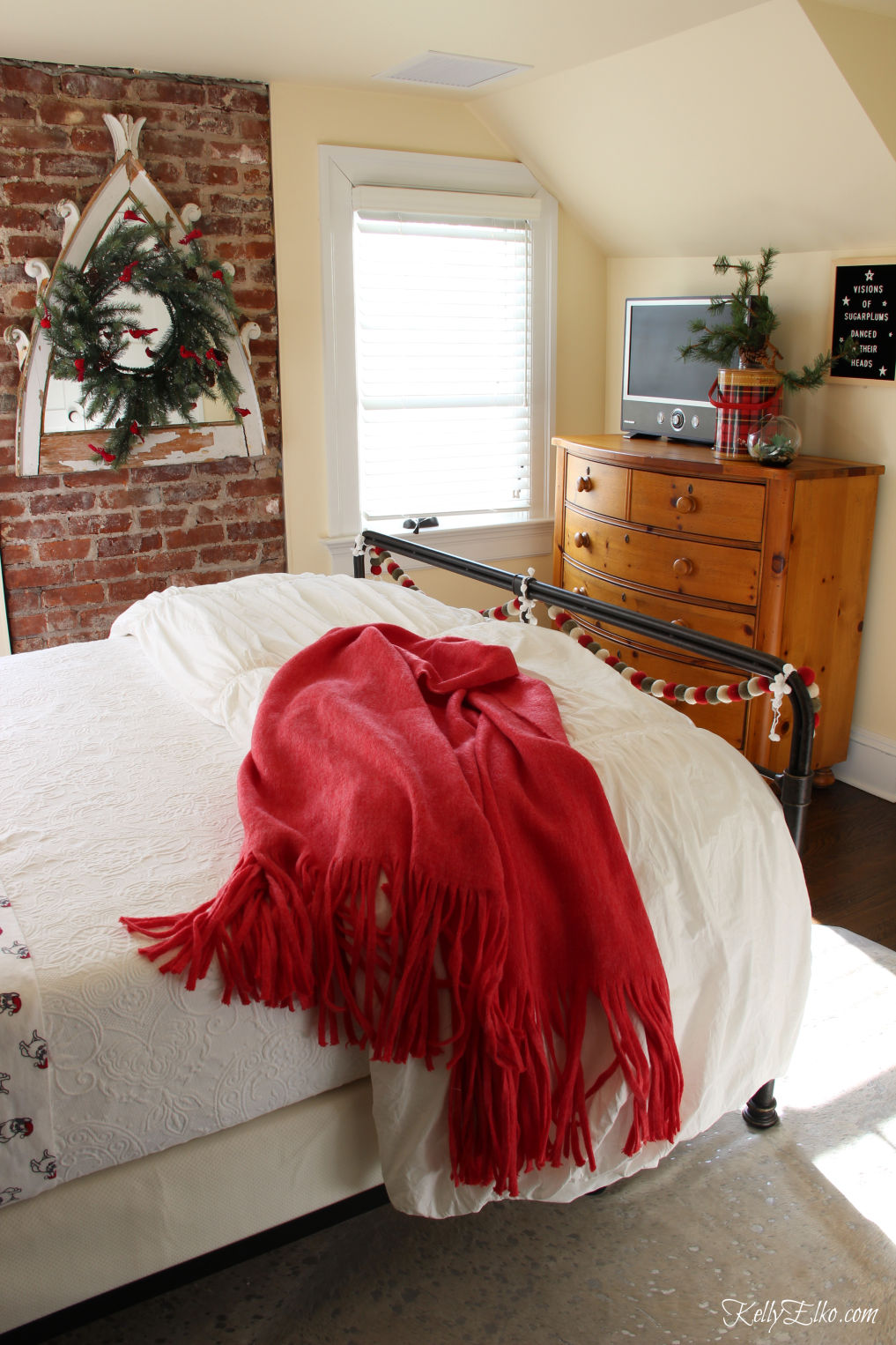 Cozy Christmas Guest Bedroom - love the flannel sheets, fringe throw and other whimsical decorating ideas kellyelko.com #christmas #christmasbedroom #christmasdecor #christmasdecorating #christmasbedding #christmaswreath #vintagechristmas