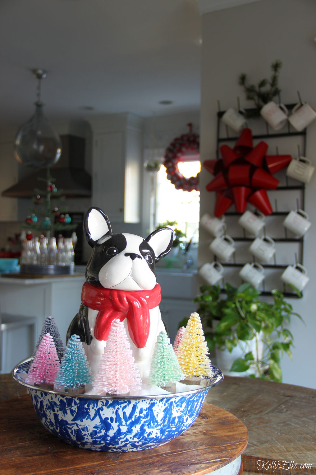 Love her festive Christmas kitchen and this adorable little dog surrounded by bottle brush trees centerpiece kellyelko.com #christmas #christmascenterpiece #christmasdecor #christmastrees #christmasdecorating #christmaskitchen #frenchbdulldog #vintagechristmas