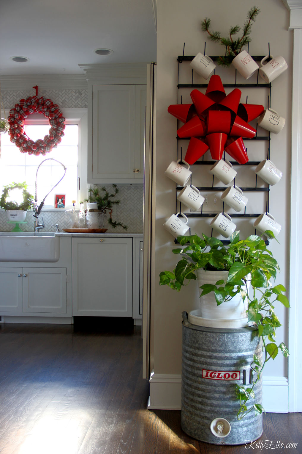 Love this Christmas kitchen with touches of red and green kellyelko.com #farmhousechristmas #christmaskitchen #christmasdecor #christmasdecorations #christmaswreath #raedunn