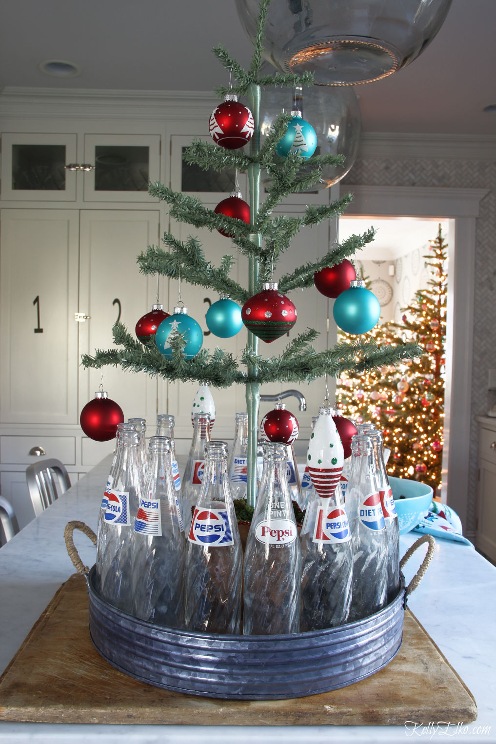 She always has the best Christmas ideas like this feather tree surrounded by vintage Pepsi bottles kellyelko.com #christmas #christmastree #christmasdecor #christmasdecorations #vintagechristmas #christmaskitchen #christmasornaments #farmhousechristmas #diychristmas #christmascrafts