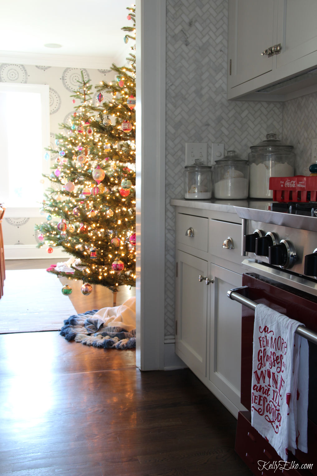 Love the pair of Christmas trees in the dining room attached to this kitchen kellyelko.com #christmastrees #christmaskitchen #farmhousechristmas #christmasdecor #christmasdecorations