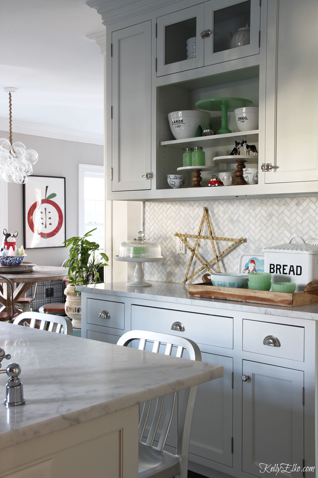 Love the open shelves in this Christmas kitchen kellyelko.com #whitekitchen #openshelves #farmhousekitchen #christmaskitchen #christmasdecor #christmasdecorations #vintagechristmas