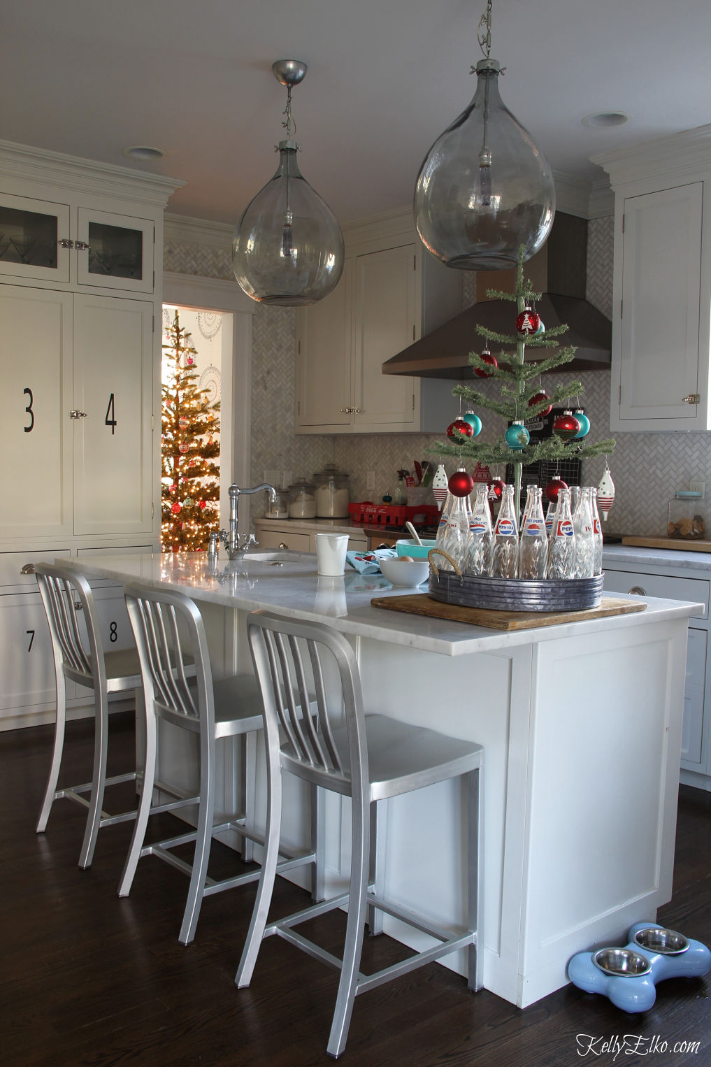 Beautiful white kitchen decorated for Christmas - love the demijohn lights kellyelko.com #christmaskitchen #farmhousekitchen #christmastree #lighting #kitchenisland #christmasdecor #christmasdecorating