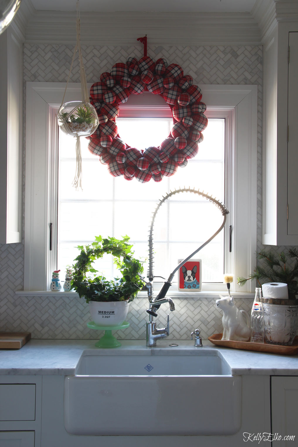 Love this huge plaid wreath in this Christmas kitchen kellyelko.com #christmaskitchen #christmaswreath #plaid #plaidchristmas #farmhousechristmas #whitekitchen #kitchensink
