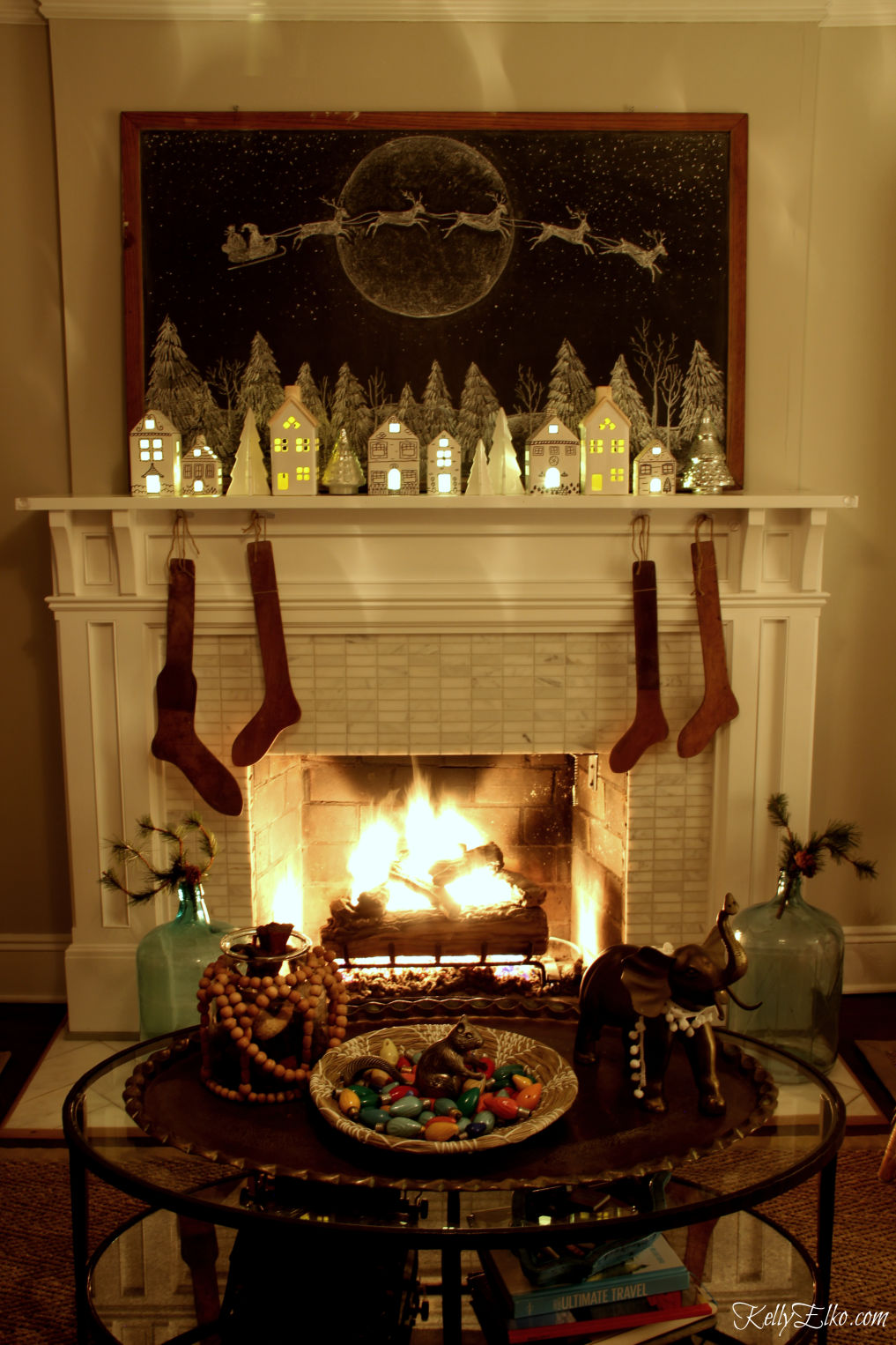 Don't miss this Christmas home tour at night! Love the glowing Christmas village and roaring fire kellyelko.com #christmas #christmslights #christmasdecor #christmasdecorating #christmasdiningroom #vintagechristmas #retrochristmas #christmastrees #christmasmantel #