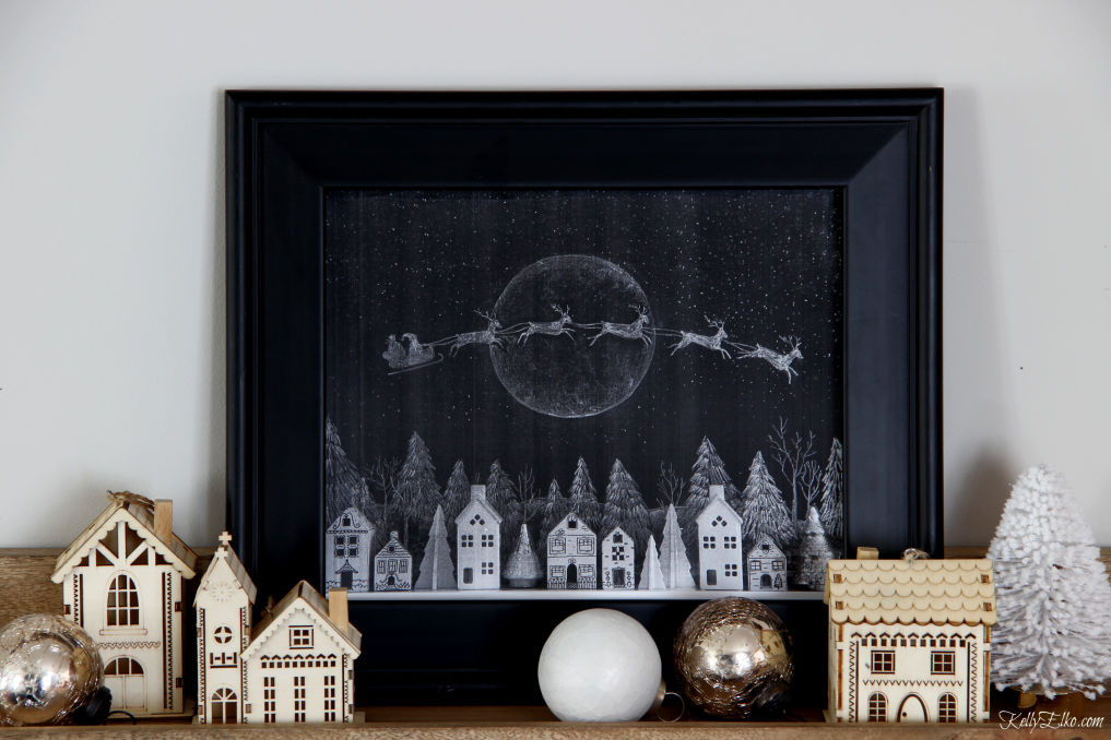 I love this free printable chalkboard Christmas Santa and reindeer flying over a village of houses kellyelko.com #chalkboard #chalkboardart #chalkart #freeprintables #printables #freeart #art #santa #christmas #christmasart #christmasprintable #christmasdecor #christmasdecorating