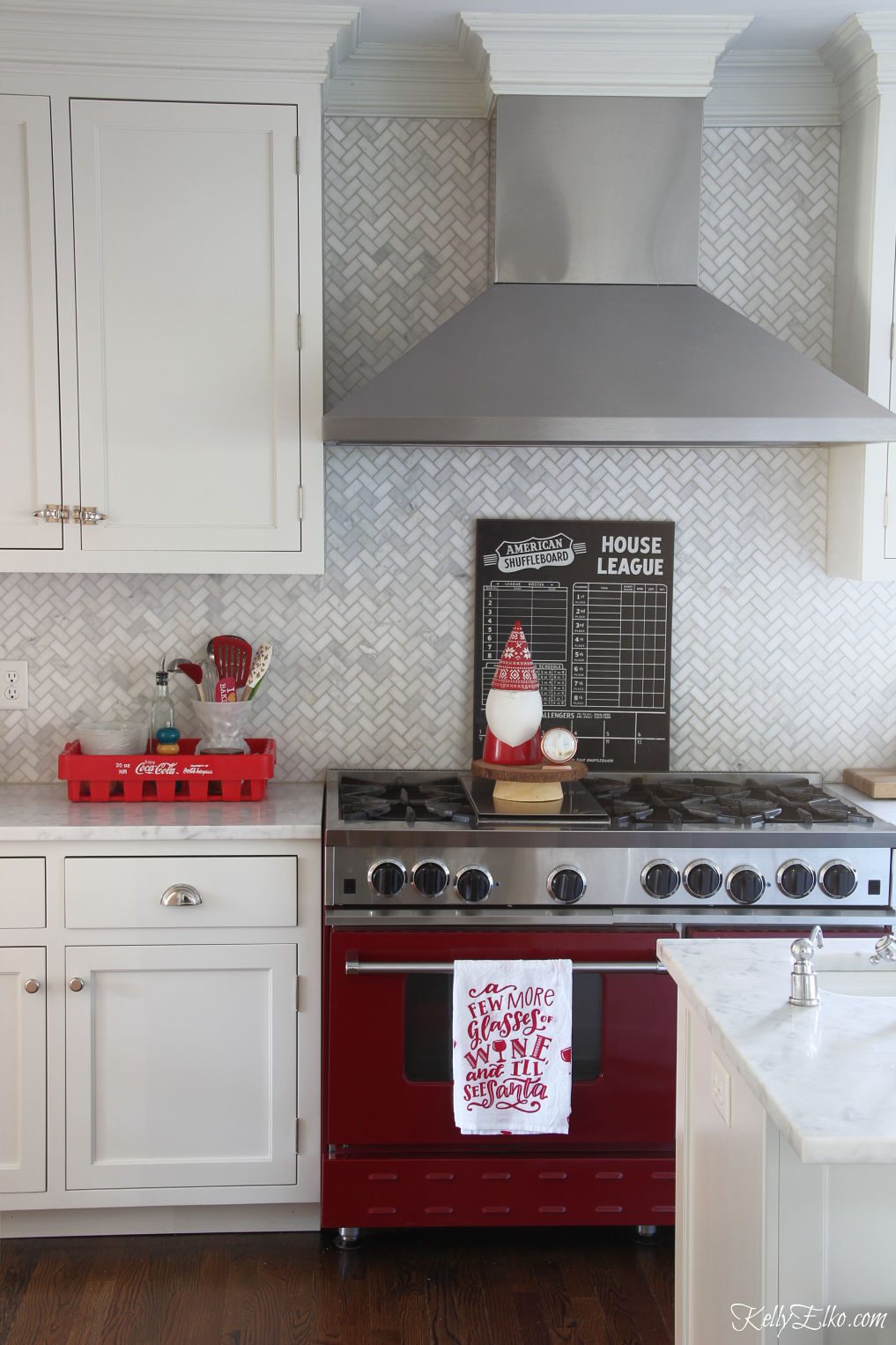 Love this red stove and white herringbone backsplash in this fun Christmas kitchen kellyelko.com #whitekitchen #herringbonetile #backsplash #christmaskitchen #christmasdecor #christmasdecorating #vintagechristmas