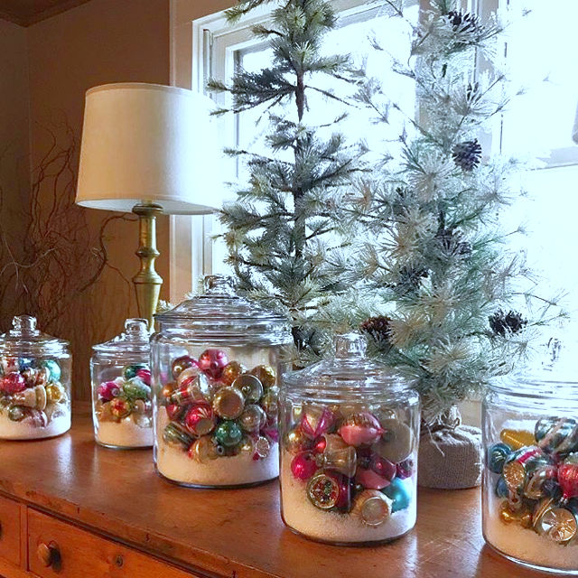 Shiny Brite Decorating Ideas - the most creative ideas for displaying Christmas ornaments like these clear glass jars filled with faux snow and ornaments kellyelko.com #vintagechristmas #christmasornaments #christmaswreath #christmasdecor #christmasdecorating #shinybrites #vintageornaments #ornaments #christmastree