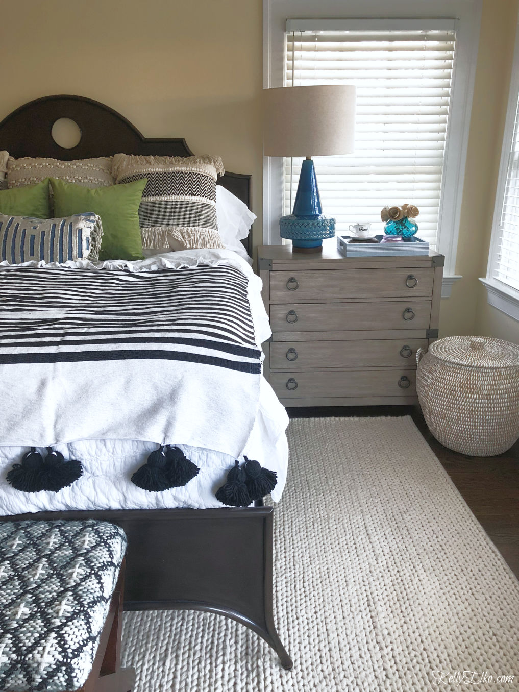 Love this bedroom and the fun tassel blanket and chest of drawers as a nightstand kellyelko.com #bedroom #bedroomdecor #bedding #boho #eclecticdecor #interiordecor #midcentury
