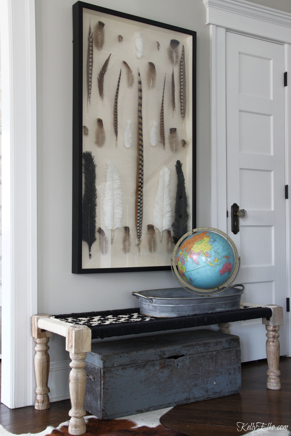 Love this huge feather shadow box in this black and white foyer kellyelko.com #foyer #foyerdecor #benches #art #shadowbox #vintagedecor #bohodecor #eclecticdecor