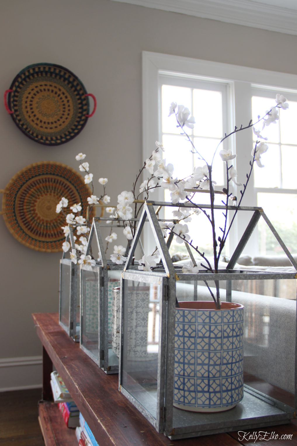 Love these lanterns filled with spring branches kellyelko.com #springdecor #spring #farmhousedecor #farmhousestyle #boho #bohostyle #familyroom #familyroomdecor