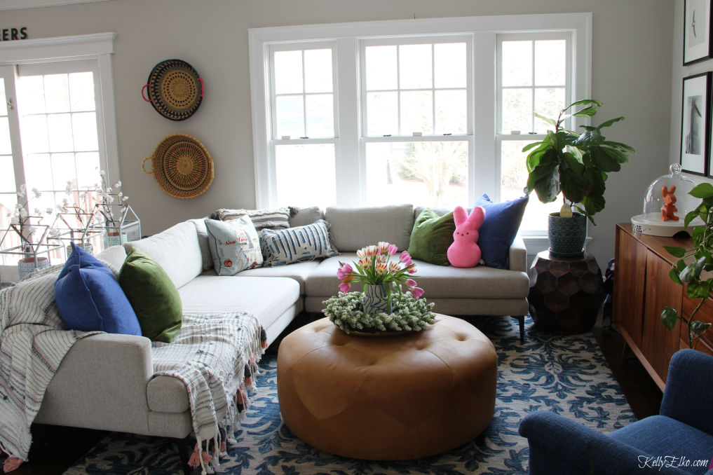 Love this cozy family room with sectional sofa, blue rug and huge leather ottoman kellyelko.com #sectionalsofa #familyroom #familyroomdecor #familyroomfurniture #ottoman #bohodecor #eclecticdecor #springdecor #peeps #fiddleleaffig