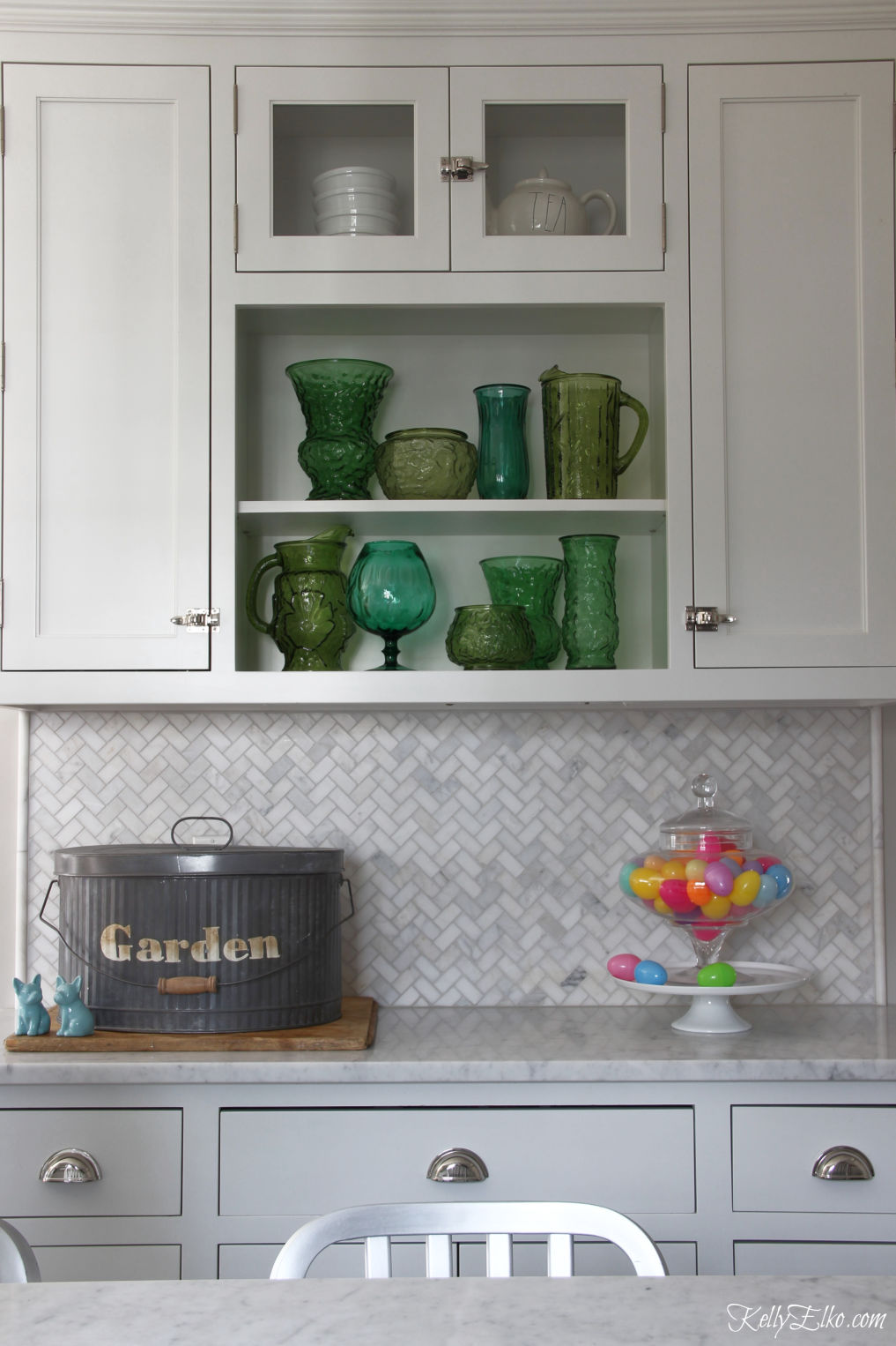 Love this white kitchen with open shelves displaying a vintage green glass collection kellyelko.com #kitchen #kitchendecor #openshelves #collection #vintagedecor #springdecor
