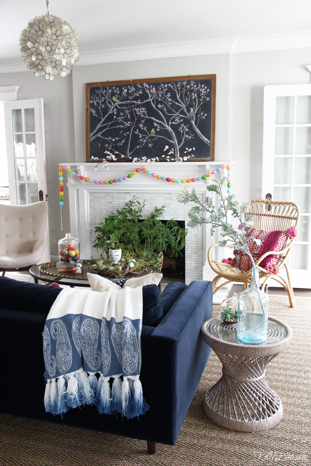Spring chalkboard mantel - love the original chalk art on the vintage chalkboard and the DIY egg garland kellyelko.com #easter #easterdecor #spring #springdecor #mantel #springmantel #eastereggs #diycrafts #eastercrafts #springcrafts #lighting #plants #rattan #boho #bohodecor