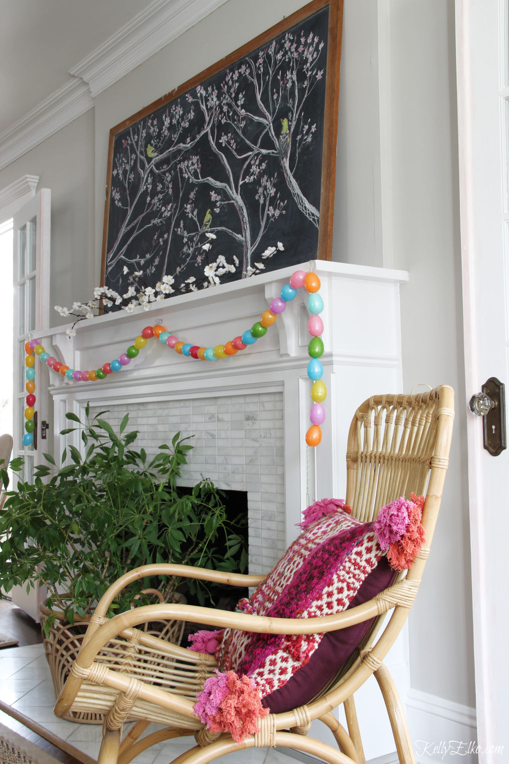 Spring chalkboard mantel - love the original chalk art on the vintage chalkboard and the DIY egg garland kellyelko.com #easter #easterdecor #spring #springdecor #mantel #springmantel #eastereggs #diycrafts #eastercrafts #springcrafts #lighting #plants