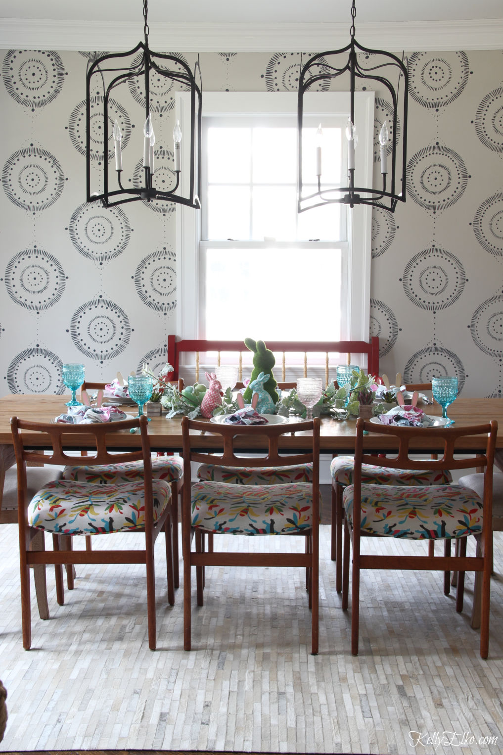 Love this hand painted wall mural and pair of huge lanterns in this dining room kellyelko.com #diningroom #diningroomdecor #murals #lighting #diningroomlighting #midcenturymodern #diningroomfurniture #ourarticle #article #bohodecor #eclecticdecor #springdecor #springtable #eastertable #cowhide #otomi