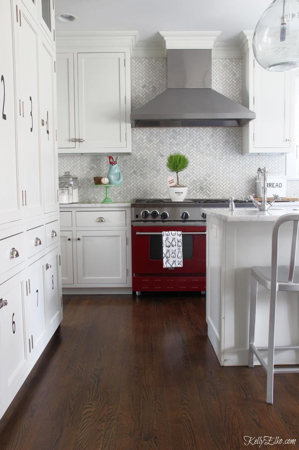 White kitchen with stunning red stove and marble herringbone backsplash kellyelko.com #whitekitchen #redstove #backsplash #farmhousekitchen #cottagekitchen #classickitchen #whitecabinets #kitchendecor #kitchenreno #kellyelko